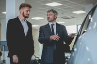 Auto showroom, vehicle manager showing new car to a buyer.