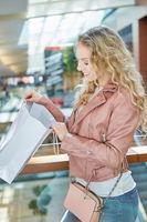 Junge Frau schaut in ihre Einkaufstüte