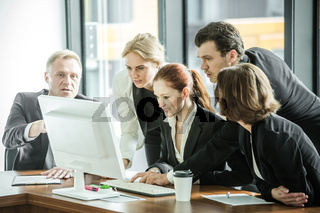Business team look at one computer monitor