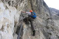 Mann steigt steile Felswand hoch