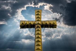 golden cross isolated with cloudy sky background -
