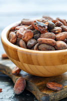 Organic cocoa beans in a wooden bowl.