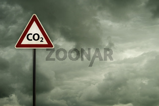 kohlendioxid - symbol auf verkehrsschild vor dunklem wolkenhimmel