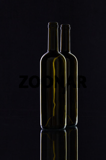 Silhouette of elegant and very old wine bottles on a glass desk