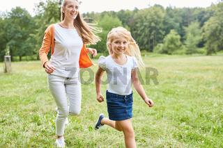Mädchen macht einen Wettlauf mit der Mutter