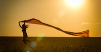 Young woman running on a rural road at sunset in summer field. Lifestyle sports freedom background