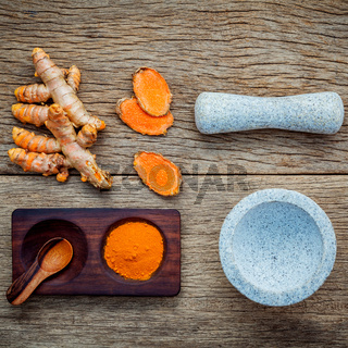Alternative ingredients for skin care. Homemade scrub curcumin powder and curcumin roots with white mortar set up on old wooden background.