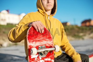 Close-up of a teenager dressed in a jeans hoodie sitting in a skate park and holding a skateboard