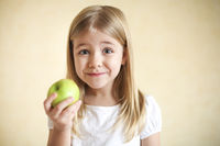 Little funny blonde girl with green apple