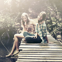 Two young fashion teen girls sitting on the bridge in a summer forest