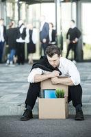 Fired businessman sitting on street