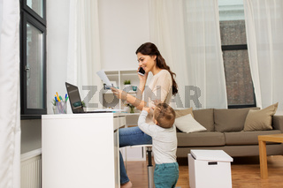 happy mother with baby and papers working at home