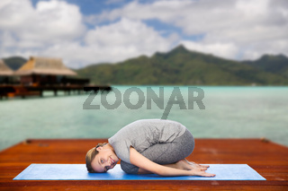happy woman making yoga in child pose outdoors