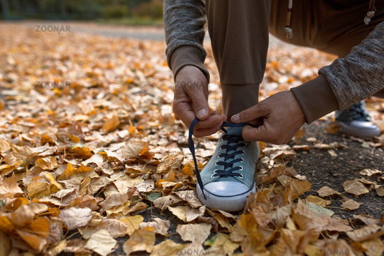 Man tying shoe laces before running outdoors.