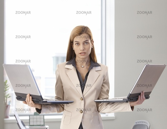Desperate businesswoman with two laptops