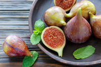 Fresh figs and mint leaves on a wooden platter.