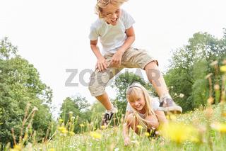Junge beim Bockspringen mit Schwester