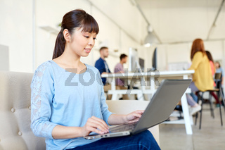 happy asian woman with laptop working at office