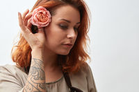 A beautiful girl with red hair decorates her hair with a pink flower, on a gray background
