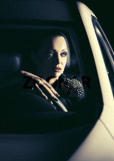 Young fashion woman driving a car in the night
