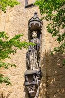 Statue aus Stein an einer gelben Fassade in Goslar