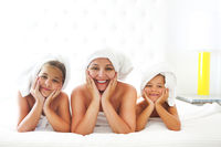 Mother and girls in bathrobes in room after shower