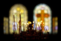 Stained glass windows in church and candles