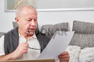 Senior als Rentner liest Unterlagen