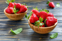 Ripe strawberries in a wooden bowls.