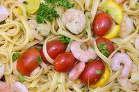 Mediterrane Küche mit Garnelen auf Bandnudeln und Tomaten