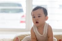 Baby boy sitting on floor.