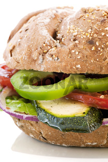 Vegetable sandwich with tomato, zucchini and onion as closeup on a white plate