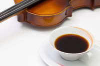 Old violin and cup of coffee on the white table