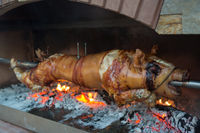 Piglet on a spit over a wood fire.