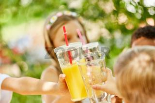 Kinder feiern und stoßen mit Saft an