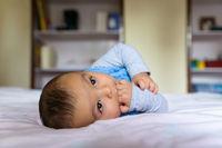 Eurasian baby on bed