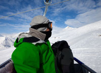 Skier on cable car and snowy ski slope