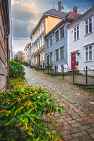 Narrow cobble stoned streets between traditional colorful houses in the old part of Bergen