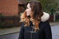 young woman wearing winter coat on suburban street