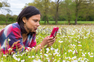 Woman lying in  meadow phoning mobile