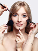 Blonde beauty female stylist - visagist with makeup brushes