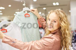 Junge Frau mit einer Auswahl von T-Shirts