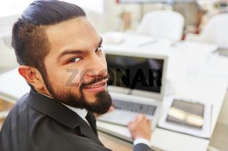 Mann arbeitet im Büro am Laptop