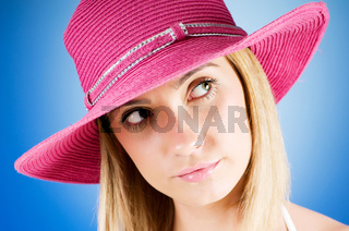 Young girl with beach hat against gradient background