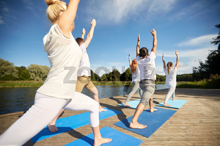 group of people making yoga exercises outdoors