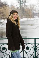 woman standing on bridge overlooking frozen river