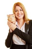 Geschäftsfrau mit Sparschwein in der Hand