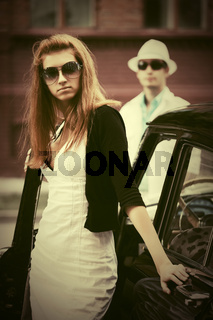 Young fashion woman in sunglasses next to vintage car