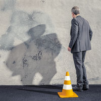 a business man facing a dirty wall
