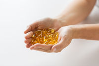 hands holding cod liver oil capsules